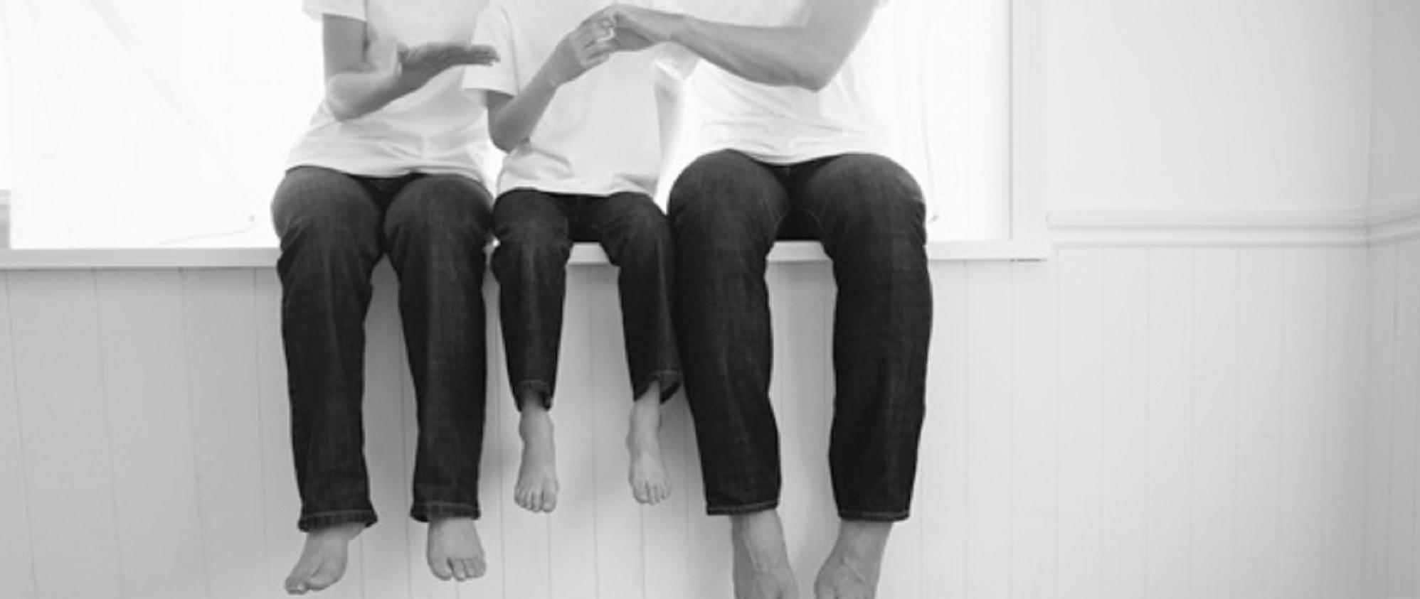 Beine von Familie mit einem Kind